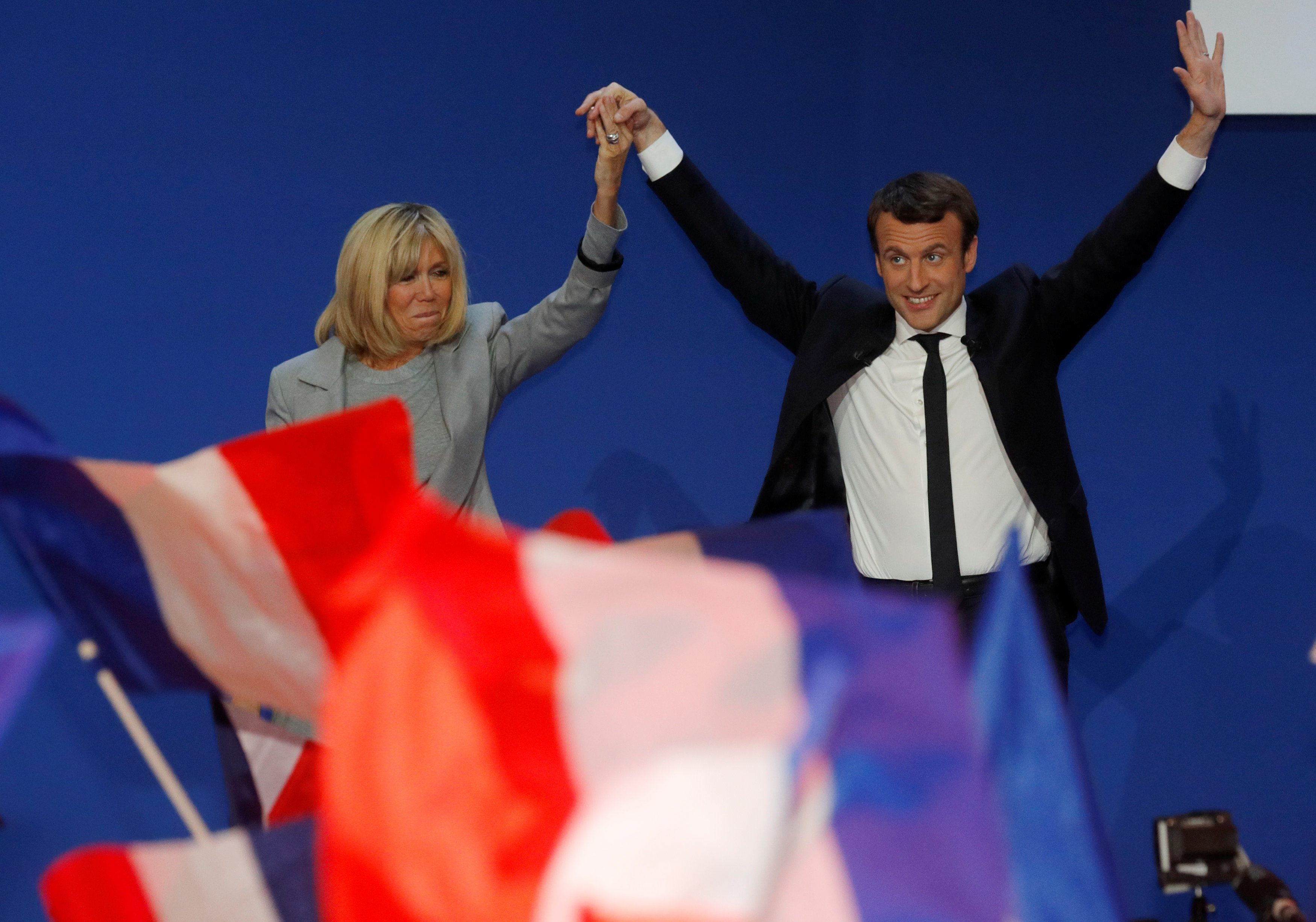 Emmanuel Macron, head of the political movement En Marche !, or Onwards !, and candidate for the 2017 French presidential election, arrives on stage with his wife Brigitte Trogneux to deliver a speech at the Parc des Expositions hall in Paris after early results in the first round of 2017 French presidential election, France, April 23, 2017. REUTERS/Philippe Wojazer