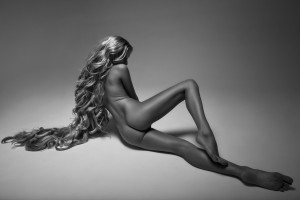 Black and white rear view of beautiful nude blonde woman with long hair lying on studio background