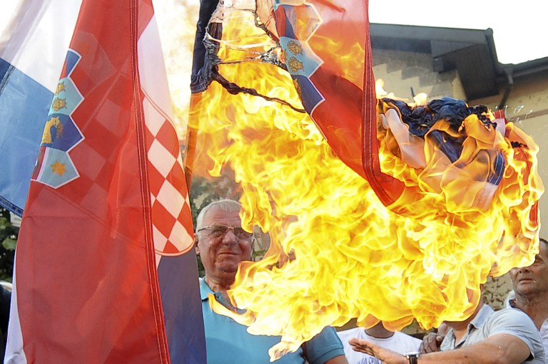 Serbian nationalist leader Vojislav Seselj (C) burns the Croatian national flag in front of the Croatian embassy during a protest in Belgrade on August 5, 2015. Zagreb cheered and Belgrade wept as they marked the 20th anniversary of Operation Storm, which ended the war sparked by Croatia's proclamation of independence from Yugoslavia and caused an exodus of Croatian Serbs. AFP PHOTO / ALEXA STANKOVIC